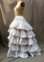 A flowing white petticoat with many ruffles on a mannequin