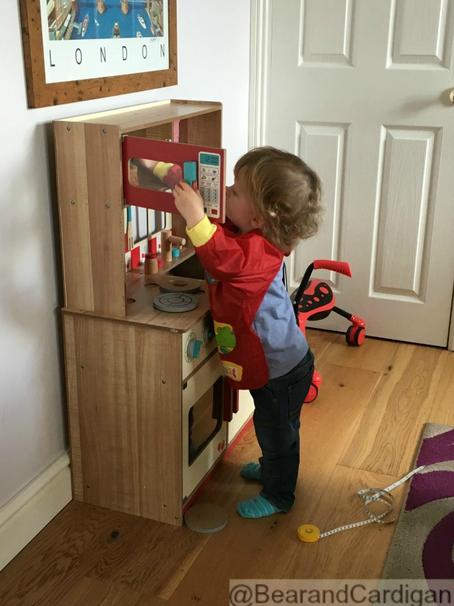 toddler opening play kitchen microwave and peering in