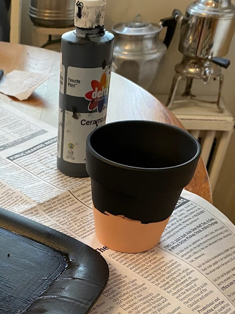 Photo of terra cotta pot being painted with black craft paint.
