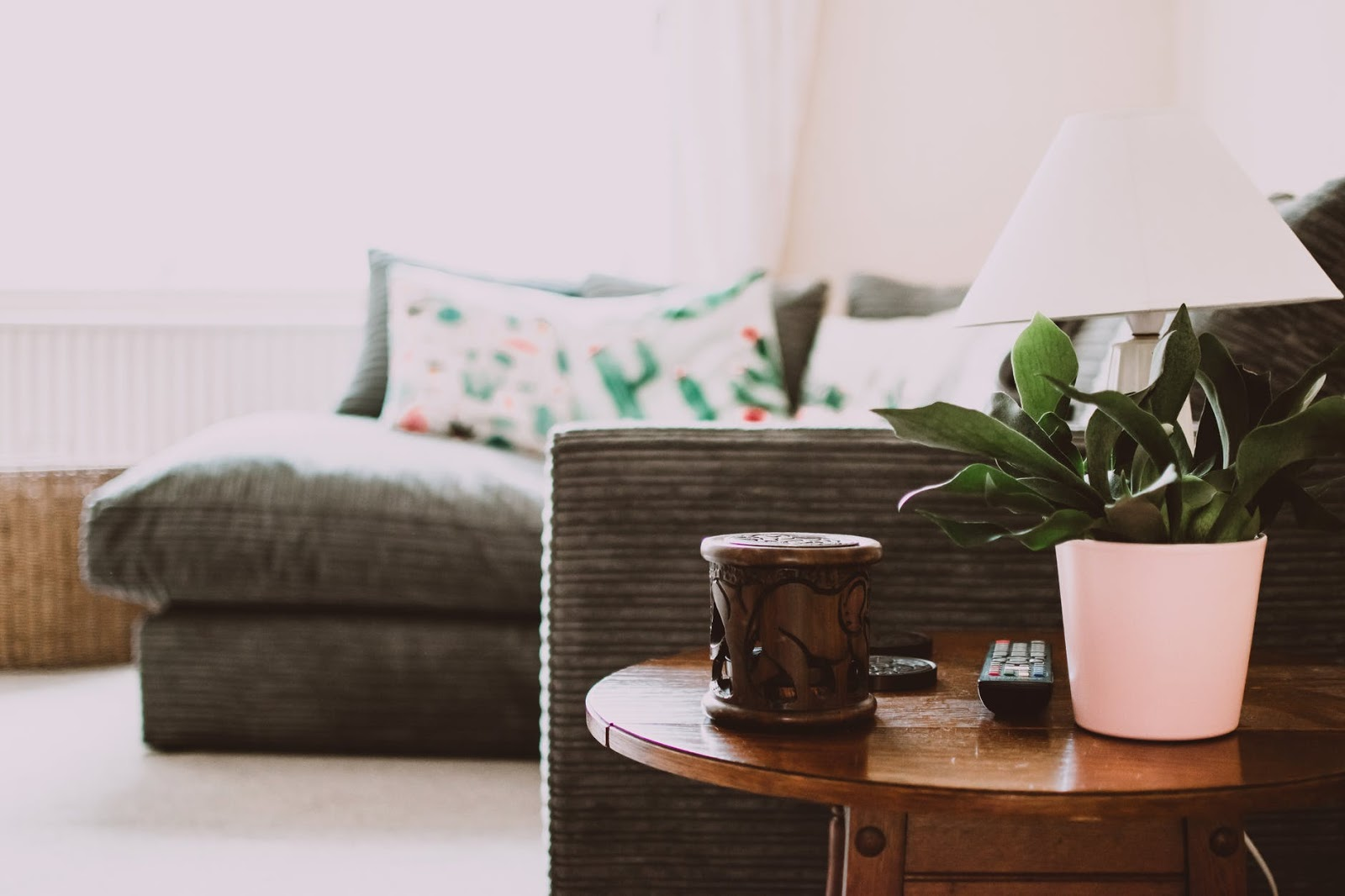 A Round Brown Wooden End Table with a plant on top and a brown L-shaped sofa in the background.