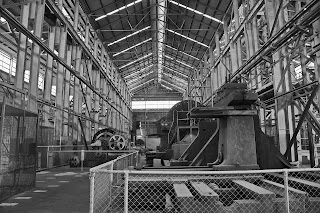 Black and white interior of a large industrial hangar with steel girder frame and fenced-off heavy industrial machinery in foreground and middle distance