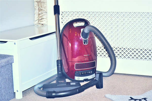 Miele Complete C3 Pure Red Bagged Cylinder Vacuum Cleaner with the upholstery brush attached to the end of the suction hose