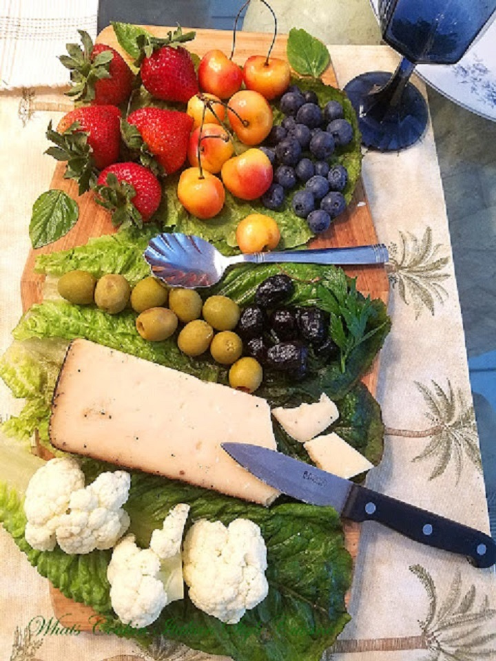 this is a wooden board with fruits, nuts and cheese