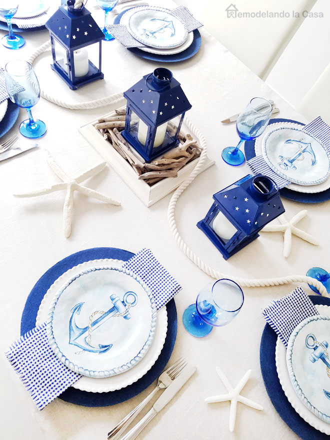 Ginham napkins, anchor salad plates from Wegmans, blue water glasses, blue lanterns, white nautical rope, driftwood pieces on table