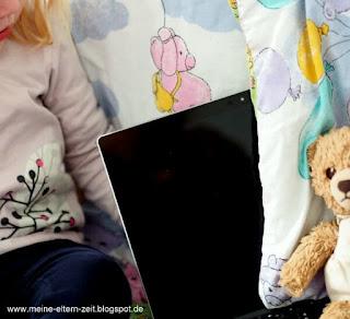 Kleinkind mit Laptop und Teddy