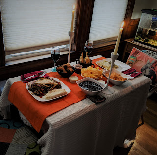 A two-person table with two wine glasses, two candles, and various food spread out including beans, rice, tortilla chips, corn, and other foods.