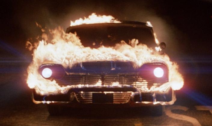 Imagem de capa: o carro Christine, com os faróis ligados e o seu capô em chamas, enquanto percorre uma estrada em auta-velocidade na noite.