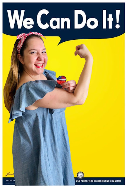 Jamie Sanders is bounding as Rosie the Riveter in a blue denim dress and red and white striped headband, in the We Can Do It poster.