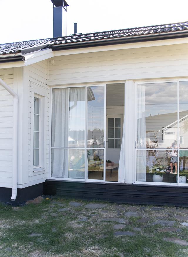 Villa H, valkoinen omakotitalo, lasitettu terassi, lumon