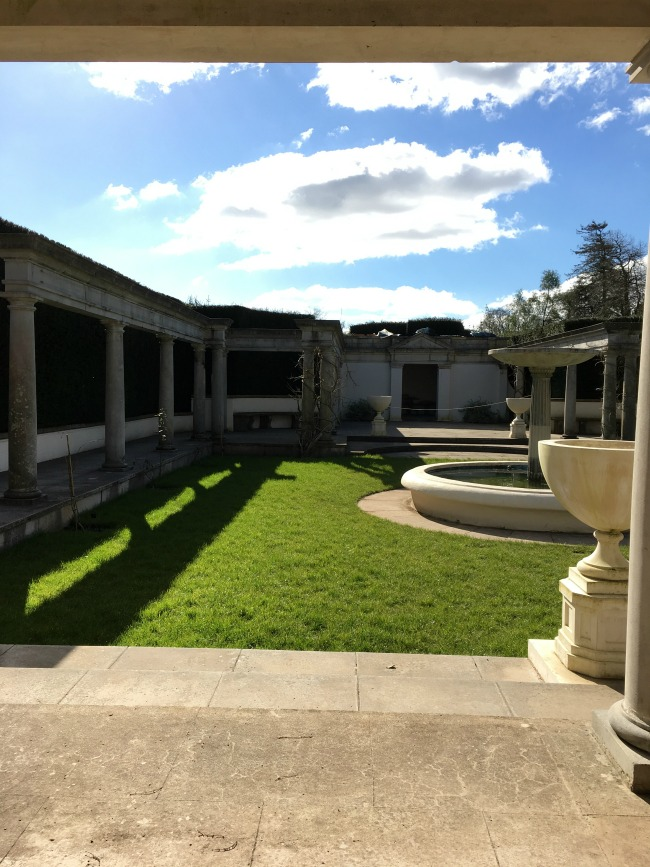 Sunshine on a small lawn with a fountain and columns
