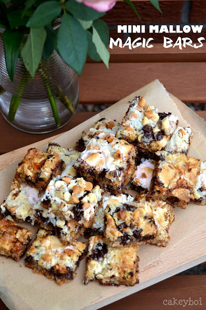 Magic bars - biscuit base, topped with walnuts, chocolate chunks, white chocolate chips, butterscotch bits, desiccated coconut, condensed milk and mini marshmallows.