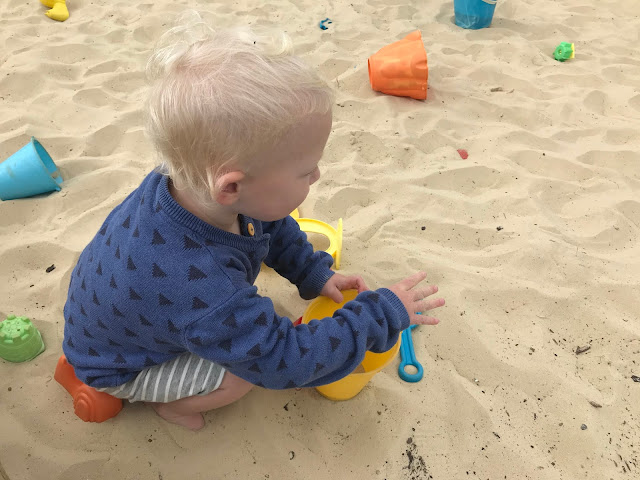 A child playing in a sandpit surrounded by plastic buckets and spades is great free summer activity