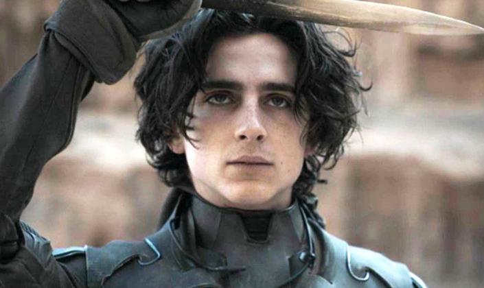 Imagem de capa: o personagem Paul Atreides, interpretado por Timothée Chalamet, um garoto branco em roupas pretas com uma armadura escura, erguendo uma faca feita de um dente ou um osso afiado, ao fundo uma rocha desértica.