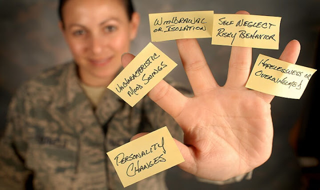 A photo of a soldier holding up her hand. On each finger is a sticky note labeling symptoms of dementia.