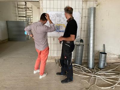 Zwei Männer vor Bauplan