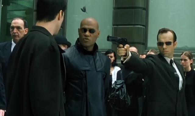 Agent Smith pointing a gun at Neo and Morpheus in the training program