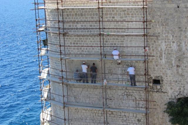 Dubrovnik, werkers aan de stadsmuur, hangend boven zee