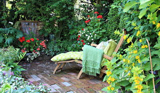 A lounge chair with green cushions on a patio surrounded by vegetation.