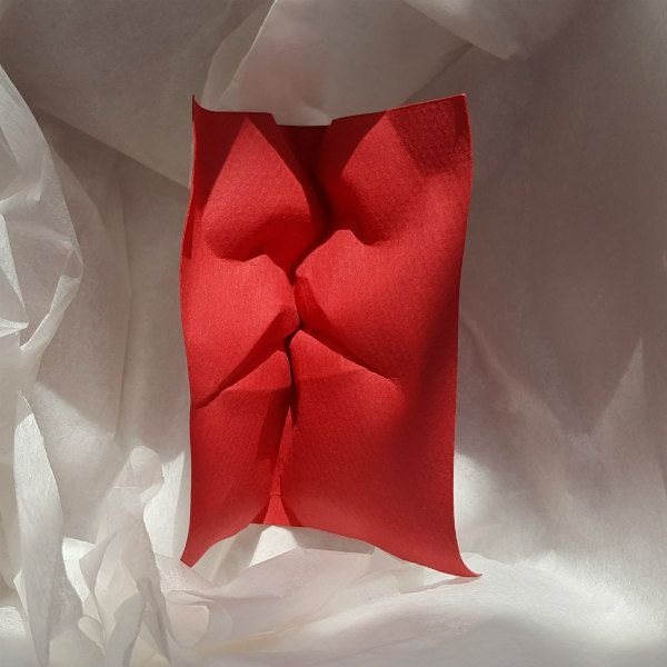 red paper sculpture details two faces kissing