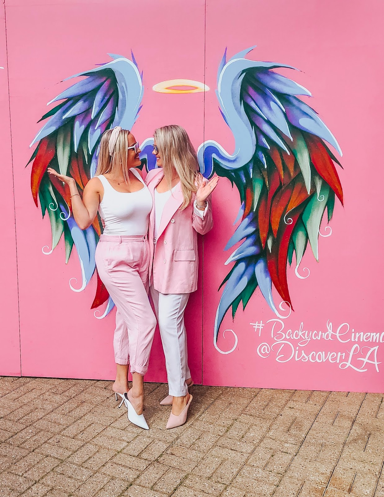 whitney and megan posing in front of angel wings on a pink wall at LA Nights, Back Yard Cinema