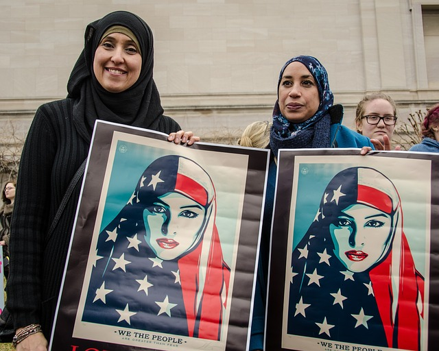 Two Muslim American women in hijabs holding hijabi US flag posters reading 'we the people'