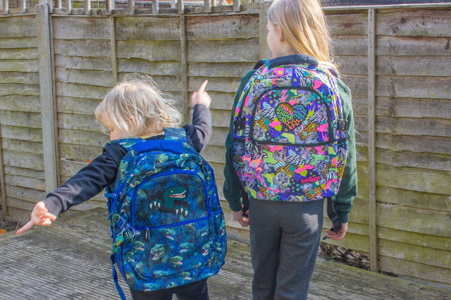 View from behind of sisters wearing Smiggle Galaxy Attach gifted backpacks in Dino and animal print