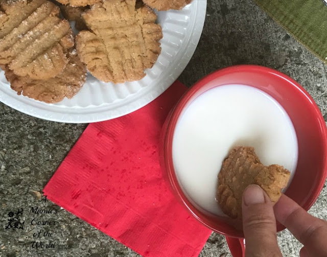 Peanut butter cookies on a plate with a cup of milk for dipping.