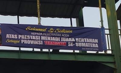 Spanduk selamat dan sukses kepada pemerintah atas prestasi menjadi juara bertahan sebagai provinsi termiskin se-Sumatera