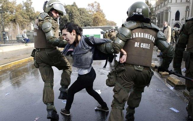 Chile - Jovem chilena é presa por policiais durante protesto no dia do trabalho em Santiago. Foto: Reuters