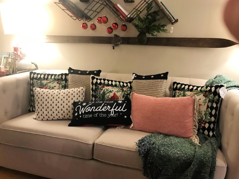a tan couch with Christmas pillows on it
