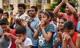 graphic கைதட்டிக்கொண்டும் சங்கூதிக்கொண்டும் மக்கள் கூட்டமாய் நிற்கின்றனர்.