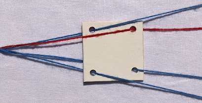 A weaving tablet with one of its threads passing through a hole in the wrong direction