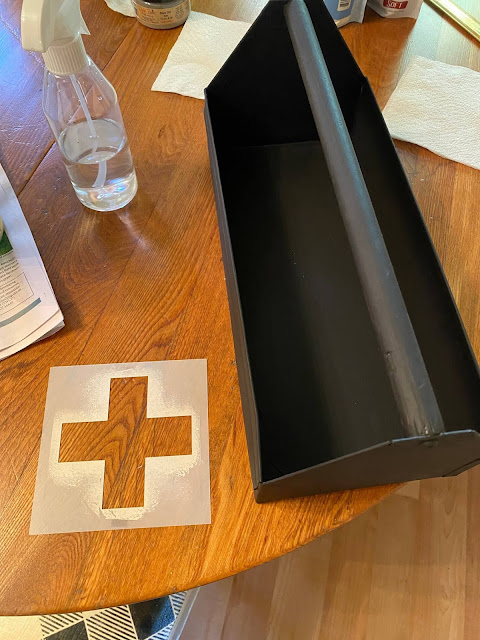 Photo of toolbox painted black and a Swiss cross stencil.