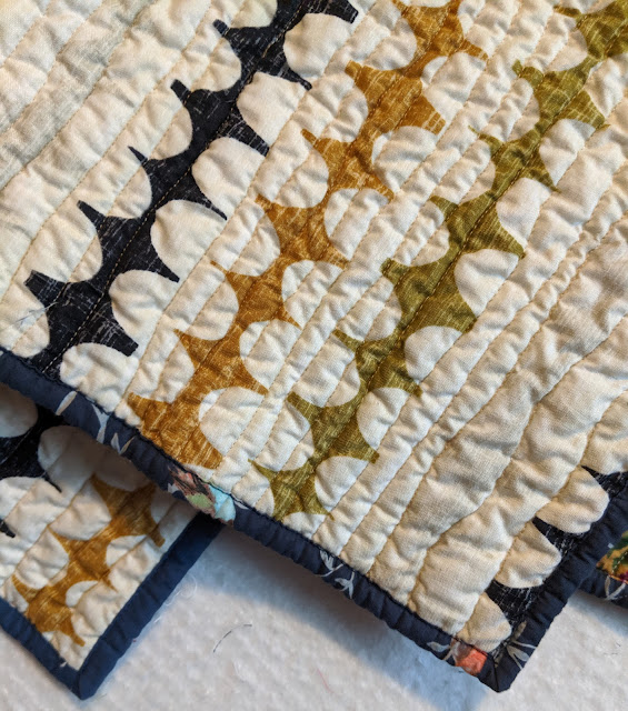 This detail highlights the organic parallel quilting lines on the background and the navy floral lawn of the binding.