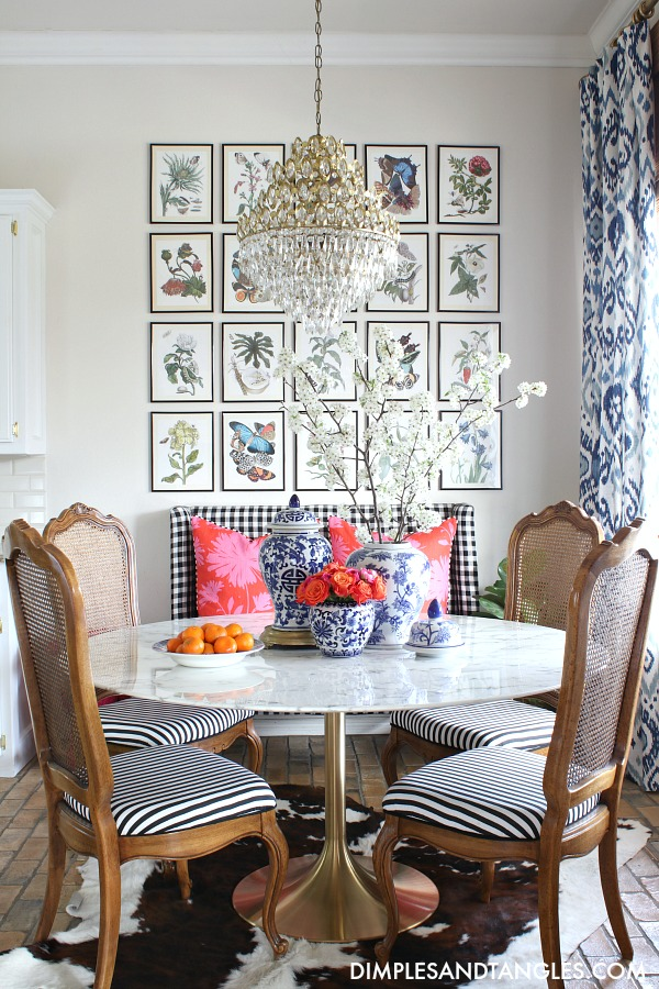 botanical gallery wall, blue and white curtains, black and white gingham chair, round marble table with brass base