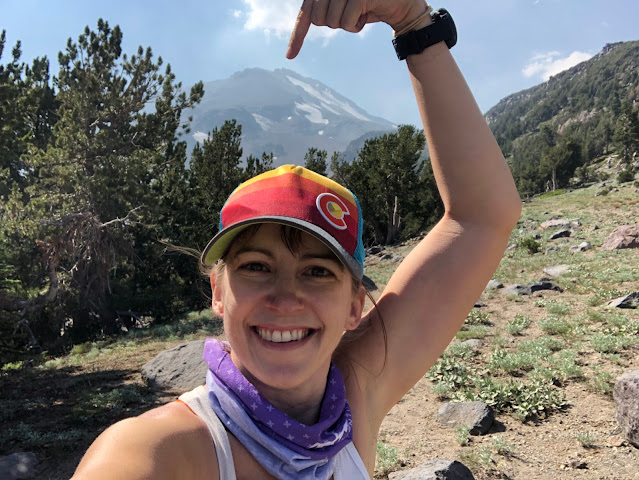 woman pointing at mountain top looming behind her