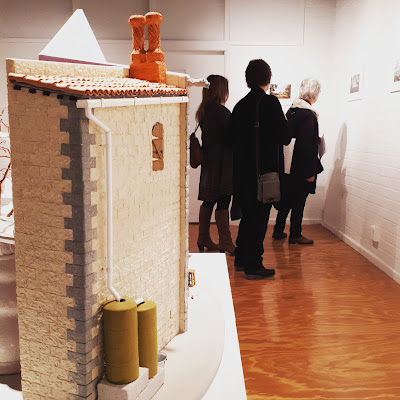 One-twelfth scale stone building on display in a gallery. In the background three woman look at pictures on the wall of the gallery.