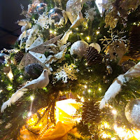 Close up of a few branches of a Christmas tree adorned with beautiful, glowing ornaments