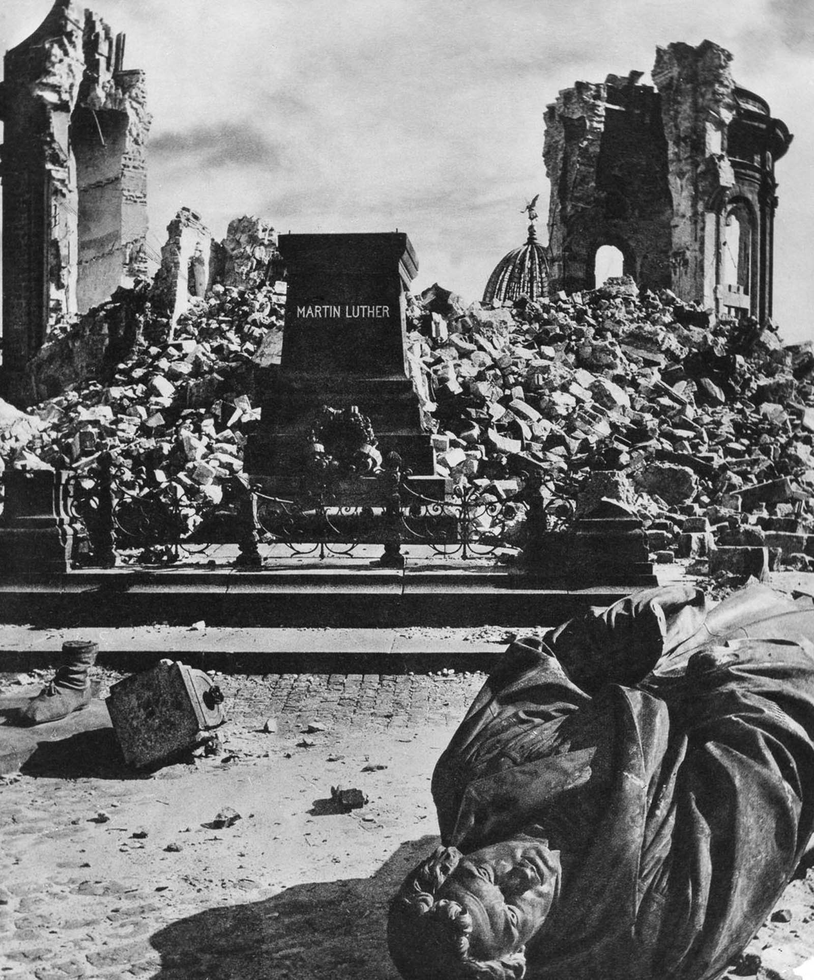 A statue of Martin Luther lies toppled in front of the ruins of the Frauenkirche. 1945.