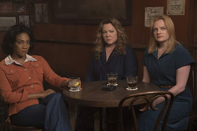 "Movie still for ""The Kitchen"" (2019) featuring Tiffany Haddish, Melissa McCarthy, and Elisabeth Moss sitting at a table in a bar"