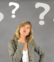 A white woman wearing a grey jacket and white top, thinking, quizzically. Above her head, question marks.