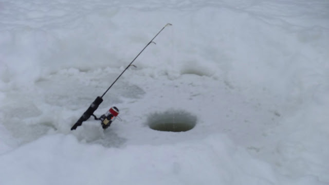 an ice fishing pole standing next to a hole cut in the ice