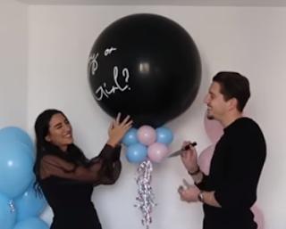Junges Paar bringt einen Luftballon zum Platzen und gibt damit das Geschlecht des Babys bekannt.