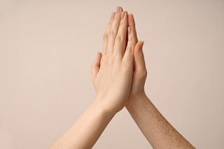 Two hands touching on a pink background.