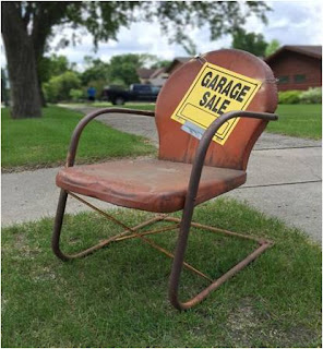 "Chair with ""Garage sale"" sign on it"