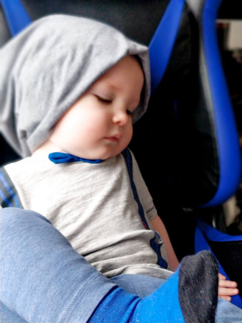 A toddler boy is sat on a black and blue gamer style high backed deck chair in a lounging position with his right leg raised up, his foot sitting flat on the seat, his left foot is resting on top with his black and blue sock sole visable. He is wearing a light blue soft fabric trouser with a grey top featuring two immitaion braces in blue and black stripes. The top also has a fabric blue bow tie attached near the neckline. He is also wearing a soft grey hat that sits above his eyebrows, covers his ears and bunches around the back of his head in a sloutch style. The boys eyes are closed and his face is looking to the left.