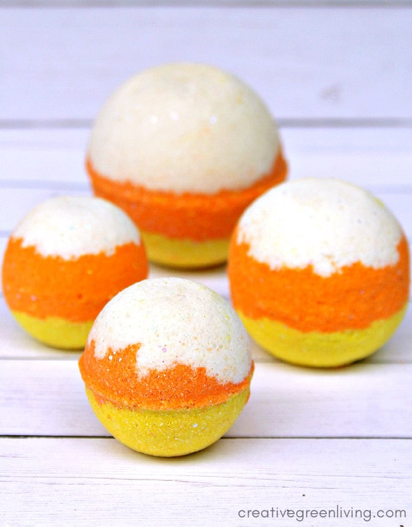 How to make easy DIY Halloween bath bombs inspired by candy corn! These pretty three colored, layered bath bombs smell like candy and are a fun Halloween craft to make with or for kids! #bathbomb #bathbombrecipe #lush #halloween #halloweencraft