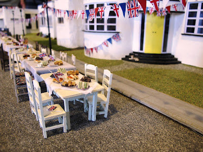 Miniature scene of a VE Day street party in front of a row of Art Deco houses.