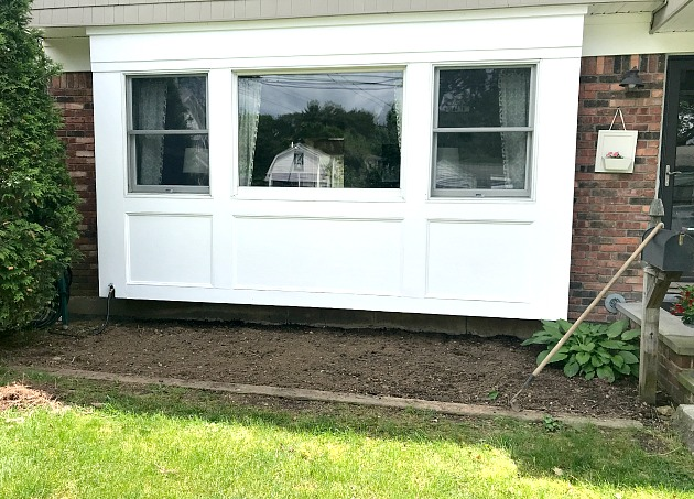 Front window of the house with garden bed