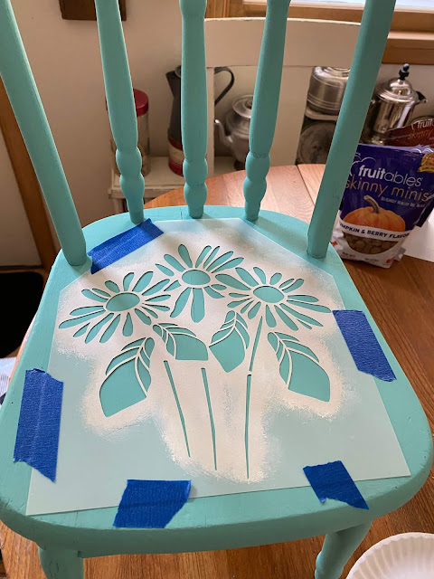 Photo of a child's chair being stenciled with a daisy stencil.